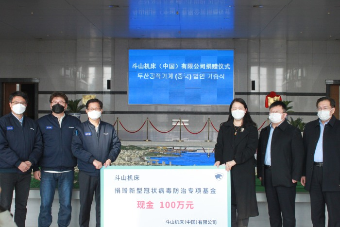 斗山机床总经理金晳俊先 生(左三)代表公司捐赠新冠防治 资金100万元